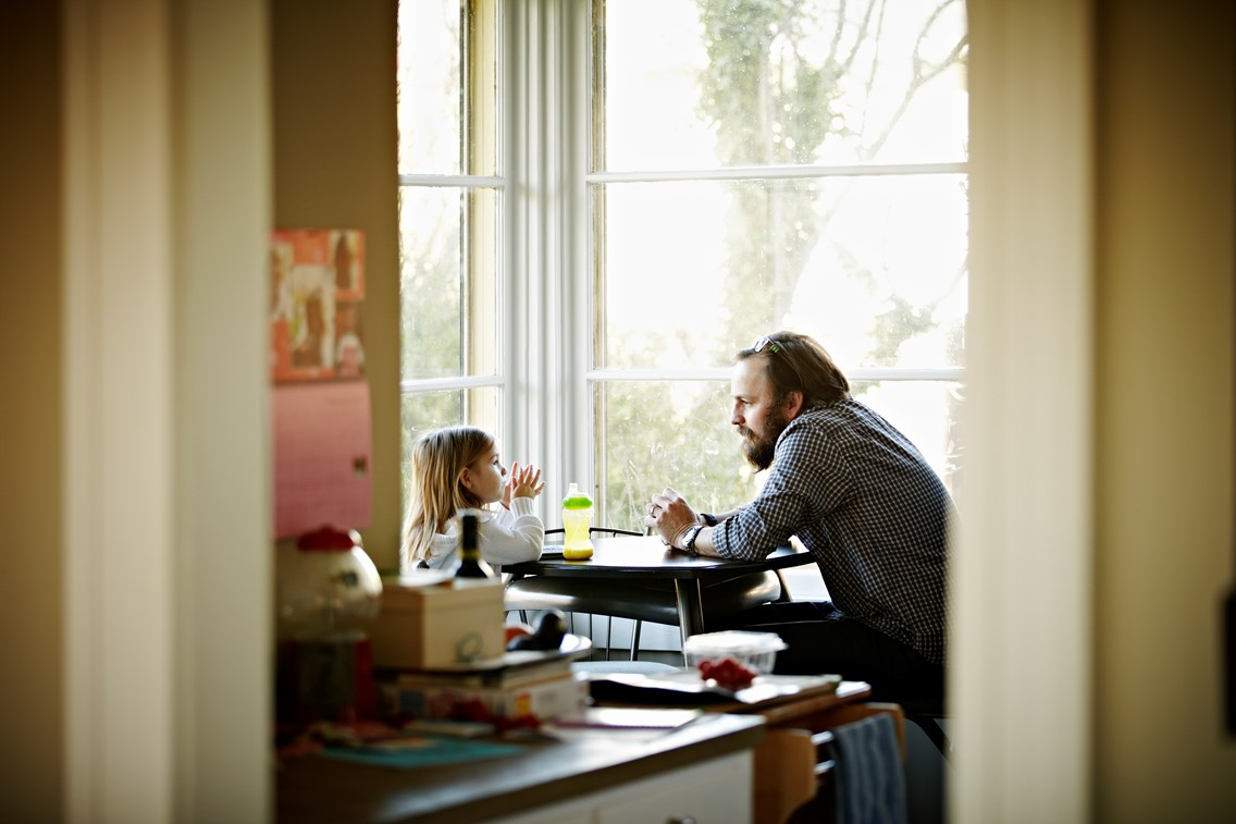 Father and daughter sitting at kitchen table near window in discussion